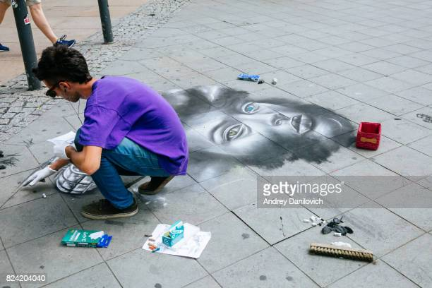 street artist painting with chalks on the street. - street artist stock photos and pictures
