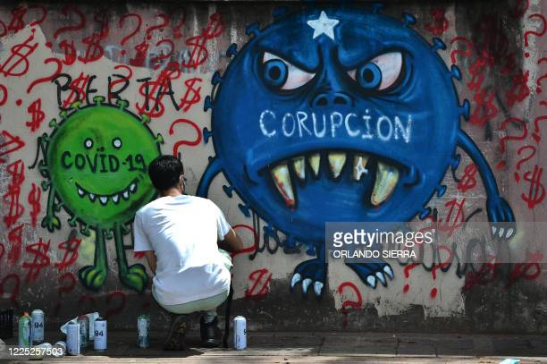 Street artist paints a mural about COVID-19 and corruption, in the surroundings of the Hospital Escuela in Tegucigalpa on July 7, 2020. - Global...