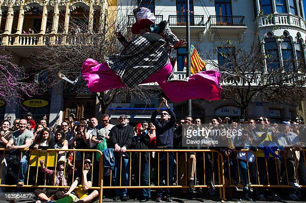 Street artist performs as people attend the 18th 'Mascleta', an explosive barrage of firecrackers and fireworks celebrating the arrival of the Spring...