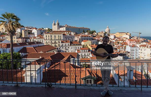 A street artist plays a 12 strings Portuguese guitar at the Miradouro de Santa Luzia above Alfama one of the city's historic neighborhoods on August...