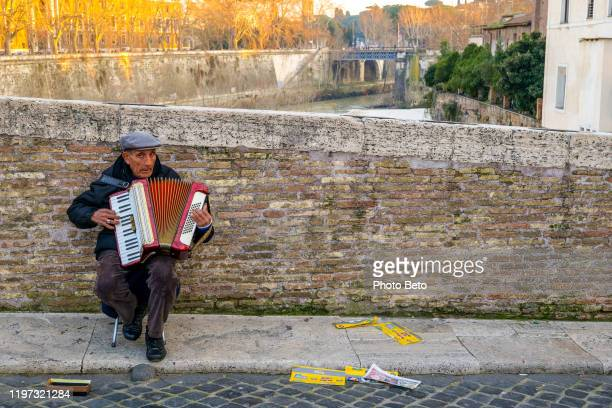 a street artist plays the accordion near the isola tiberina in rome - street artist stock pictures, royalty-free photos & images