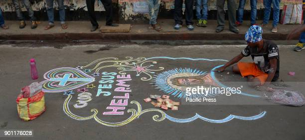 A street artist sketching the picture of Jesus Christ with colorful chalks ahead of the Christmas festival