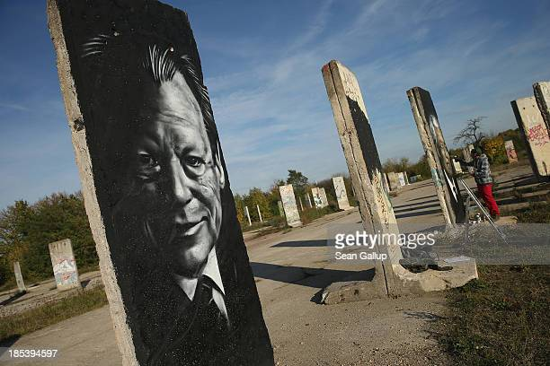Street artist Victor Landeta spray paints a portrait of former South African leader and human rights activist Nelson Mandela on a sliver of the...