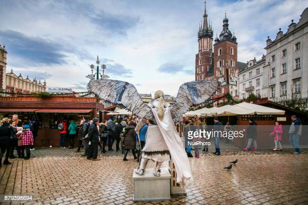 A street artist wearing angel's costume poses near a traditional Christmas Market at the Main Square in Krakow Poland on November 25 2017