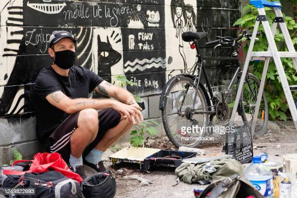 """street artist working in backstreet alley. - """"martine doucet"""" or martinedoucet stock pictures, royalty-free photos & images"""