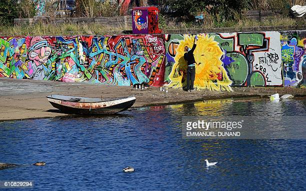 A street artist works at at the NDSM shipyards in Amsterdam on September 27 2016 / AFP / EMMANUEL DUNAND / RESTRICTED TO EDITORIAL USE TO ILLUSTRATE...