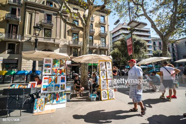 street artists and tourists in barcelona, spain - street artist stock photos and pictures