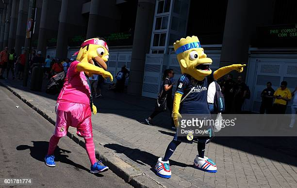 Street artists dressed as the cartoon figure Bart Simpson try to animate football fans to take photos of them at the estadio Santiago Bernabeu ahead...
