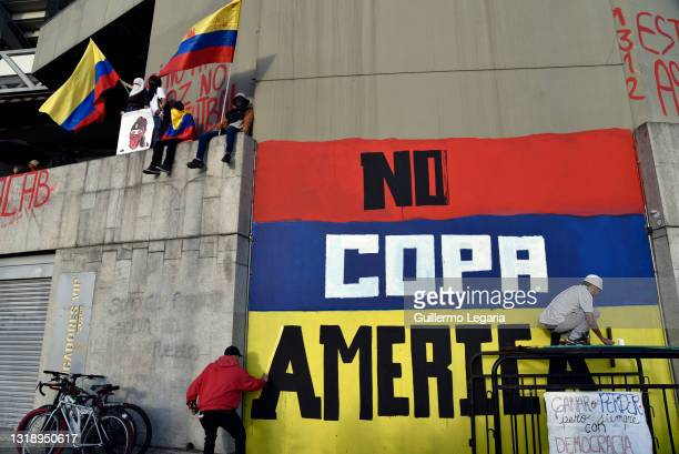 Street artists paint a graffiti against Colombia being the host of Copa America on a wall of the Campin Stadium during a protest as part of a...