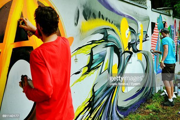 Street Artists Spraying Graffiti On Wall