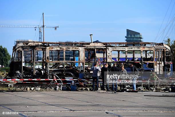 Street artists work at the NDSM shipyards in Amsterdam on September 27 2016 / AFP / EMMANUEL DUNAND