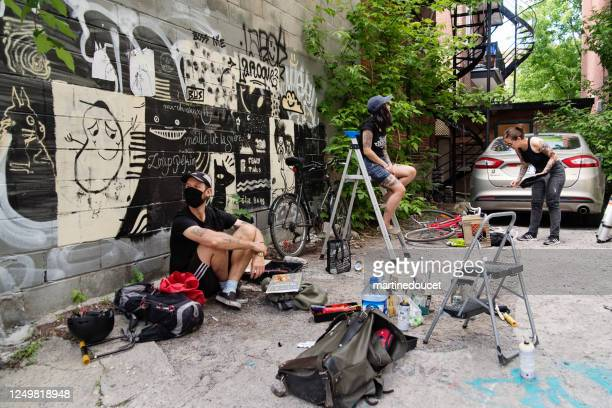"""street artists working in backstreet alley. - """"martine doucet"""" or martinedoucet stock pictures, royalty-free photos & images"""