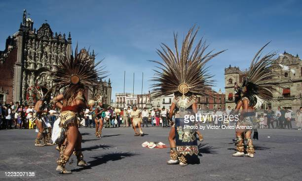 street aztec dancers wearing plume of feathers in a circle performing in zocalo square in front of the cathedral and the palacio nacional de méxico (mexico national palace) in mexico city - victor ovies fotografías e imágenes de stock