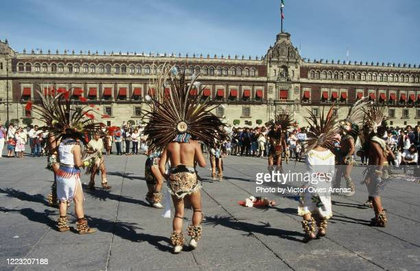 street aztec dancers wearing plume of feathers in a circle performing in zocalo square in front of the palacio nacional de méxico (mexico national palace) in mexico city - victor ovies fotografías e imágenes de stock