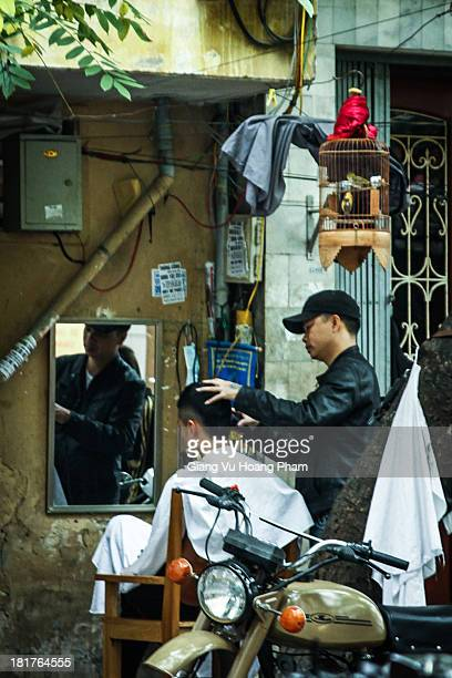 CONTENT] A street barber is making a new haircut for his customer at his barber shop on a pavement in Hanoi It's very cheap easy to find and...