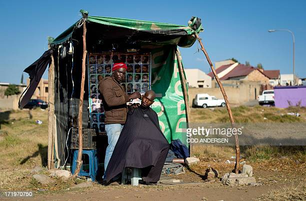 Street barber Isaac cuts the hair of a customer in his barber shop in the Diepkloof area of Soweto on June 30 2013 AFP PHOTO / ODD ANDERSEN
