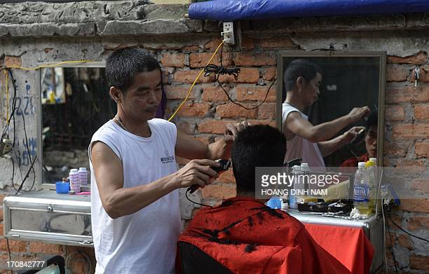 A street barber serves a customer at his walkside openair shop in Hanoi on June 19 2013 A hair cut here costs just 150 USD half or one third the rate...