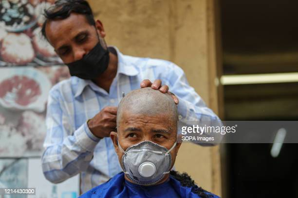 Street barber shaving a man wearing a face mask as a precaution, during the 59th day of a nationwide lockdown. As a preventive measure against the...
