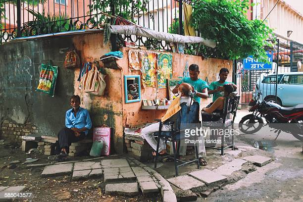 Street barbers in New Delhi India giving their customers a shave while another man waits for a haircut