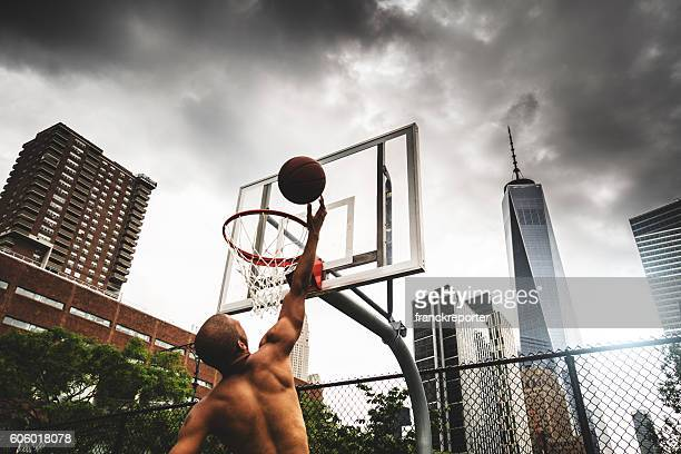street basketball player doing a slam dunk