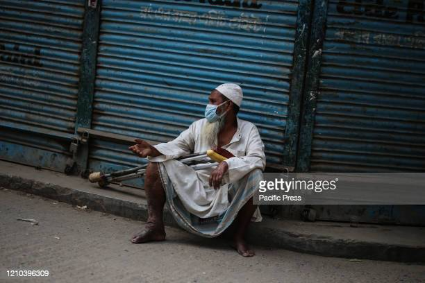 A street beggar wearing face mask in the street In this health emergency situation the most affected people are the homeless people and the beggars...
