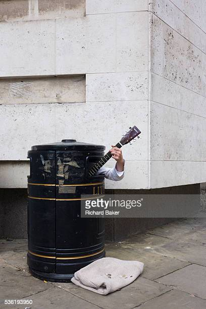 A street busker hides in a litter bin to earn extra cash as passersby hear his music on a Cambridge pavement Playing his acoustic instrument we see...