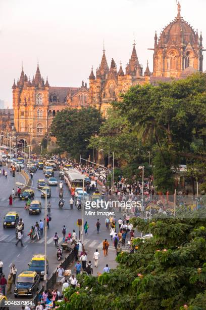 street busy with car and pedestrian traffic outside a railway station. - mumbai stock pictures, royalty-free photos & images