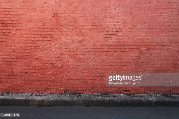 street by brick wall - brick wall stock pictures, royalty-free photos & images