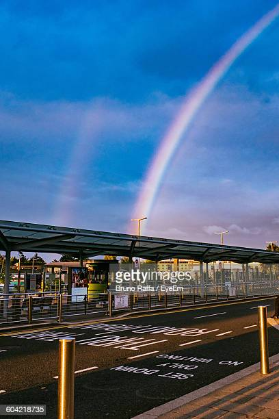 Street By Covered Walkway At Airport Against Sky With Rainbow