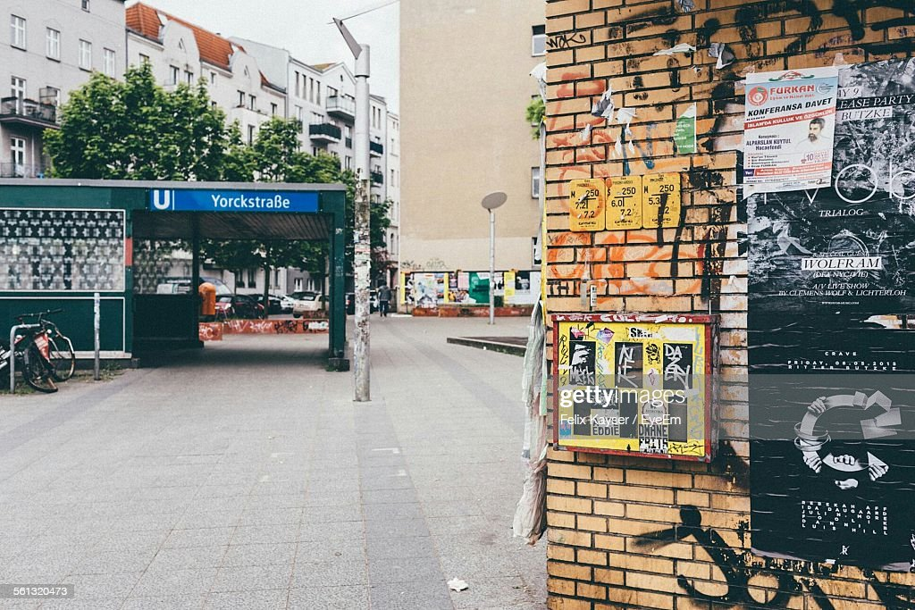 Street By Graffiti Wall Leading Towards Buildings In City : ストックフォト