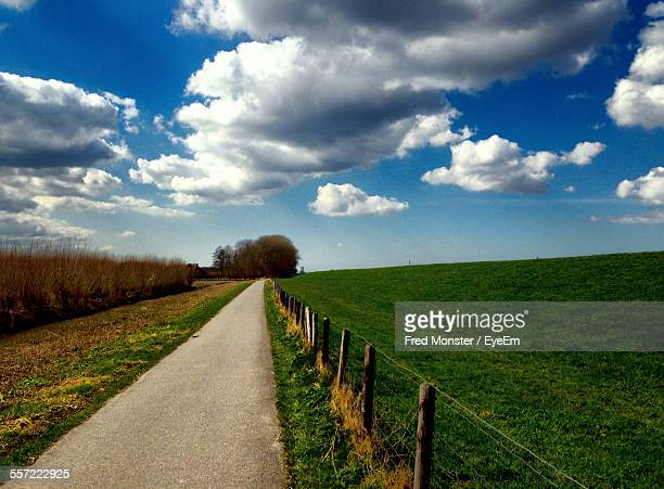 Street By Grassy Landscape Against Sky