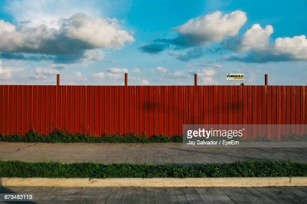 Street By Red Fence Against Sky