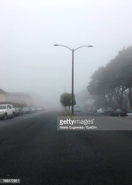 Street By Road Against Sky During Foggy Weather
