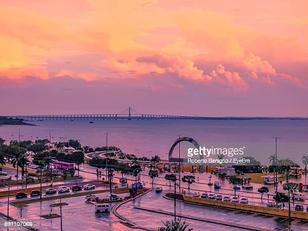 street by sea against sky during sunset - manaus stock pictures, royalty-free photos & images