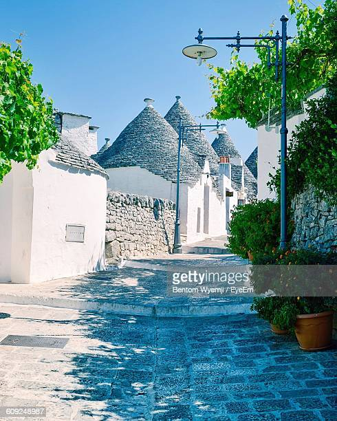 street by trulli houses against sky at alberobello - alberobello stock photos and pictures