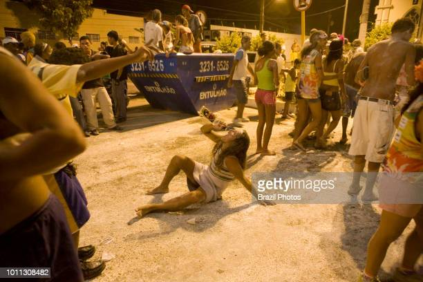 Street Carnival in Brazil man in woman's clothes drinks cachaca community party known as Carnavila at Vila de Ponta Negra quarter in Natal city Rio...
