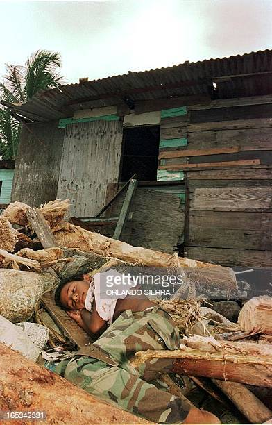 Street child in the port of La Ceiba, Honduras, sleeps amidst rubble left by Hurricane Mitch, 02 November. More than 1,700 people are reported dead...