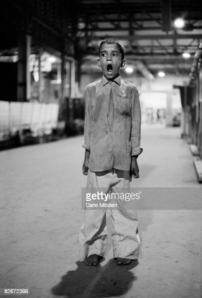 A street child stands tired in the late evening on the platform at Bombay Central Train Station India