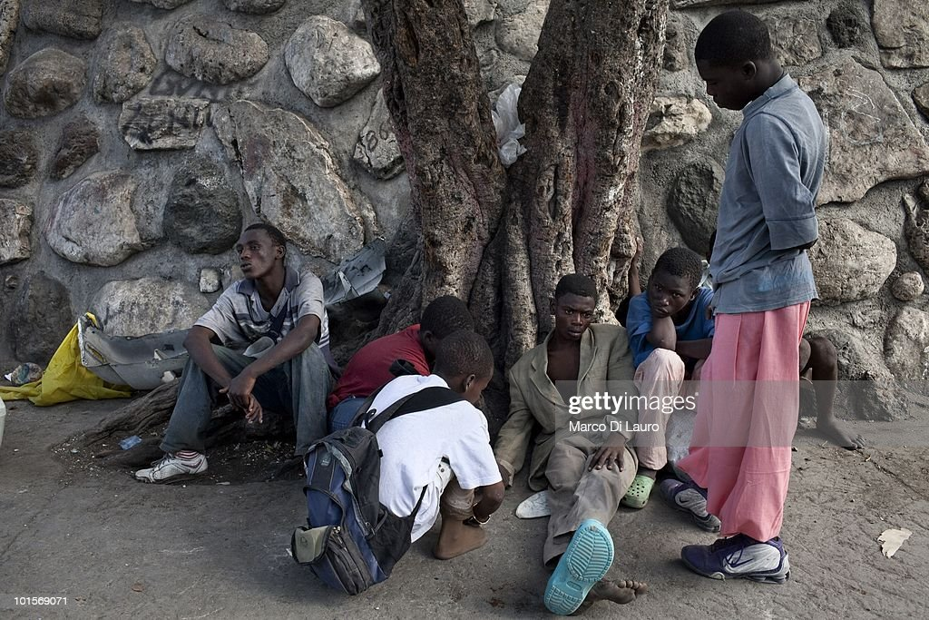 Street Children are seen in front of the Presidential Palace on February 2, 2010 in Port Au Prince, Haiti. A group of around 15 children live on the street opposite the collapsed presidential palace. Several lost both parents in the earthquake. They sleep, find food and spend their days together. mostly gambling with few coins. The oldest Simon is 18-years-old and the youngest Daniel is 13-years-old. They are only boys in their group, most of the girls they knew died in the earthquake. As many as 200,000 people died on January 12 as a consequence of the 7.0-magnitude earthquake. At least 130 people have been pulled alive from the rubble. An estimated 1.5 million people have been left homeless. The Haitian government is planning to relocate some 400,000 people, currently in makeshift camps across the capital, to temporary tent villages outside the city. Aid agencies are still struggling to supply food and water to survivors, while thousands of Haitians who suffered serious injuries remain in need of urgent medical attention.