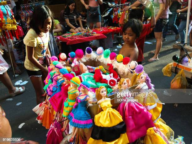 CHINATOWN MANILA PHILIPPINES Street children catch their attention with a barbie dolls collection from a toy vendor Filipinos celebrated the Chinese...