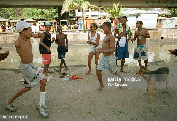 Street children enjoy a rare few minutes of fun as they dance capoeira together by a canal in the Rodoviaria district of downtown Rio De Janeiro...