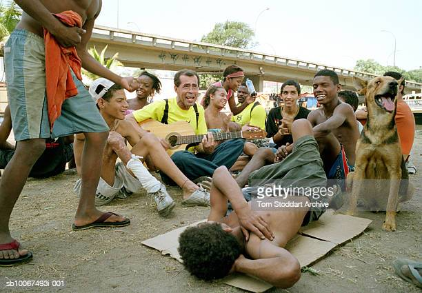 Street children enjoy a rare few minutes of fun as they sing songs with a guitar playing aid worker Georges Paixao who is from the San Martino...