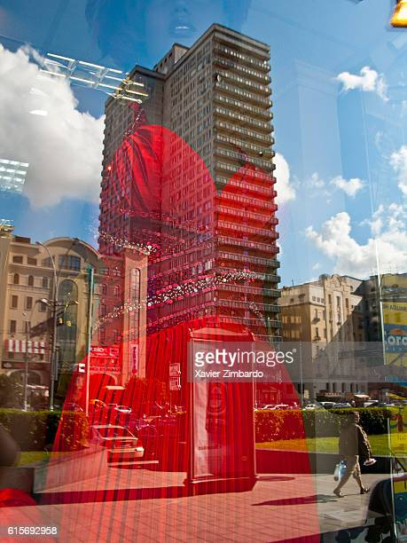 Street city life and Soviet old grey building reflected in shop window of a supermarket selling lipsticks luxury clothes and cosmetics at New Arbat...