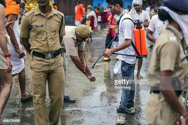 A street cleaner carrying a spray pack of Dettol disinfectant produced by Reckitt Benckiser Group Plc assists a police officer cleaning his hands in...