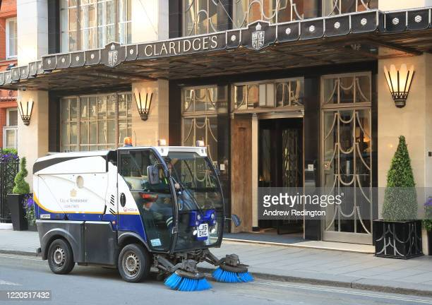A street cleaner is pictured outside the closed up Claridge's hotel on April 23 2020 in London England The British government has extended the...