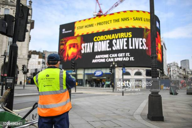 A street cleaner is seen in front of Coronavirus messaging on Picadilly Circus on April 8 2020 in London England Prime Minister Boris Johnson was...