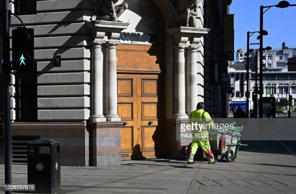 A street cleaner passes a temporarily closed hairdressers salon in Manchester north west England on March 25 after Britain's government ordered a...