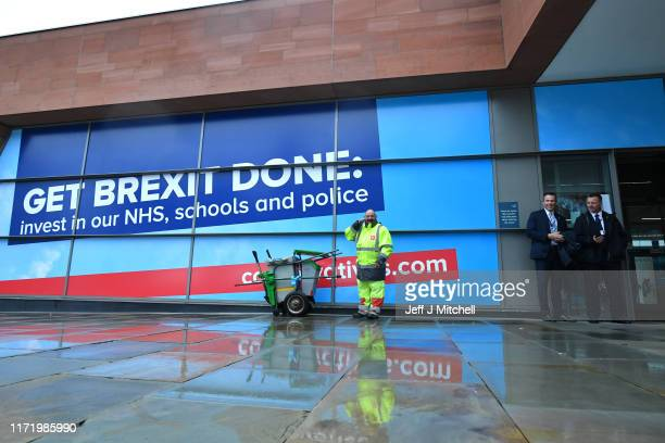 A street cleaner stands in front of a Get Brexit Done poster as delegates arrive for the Conservative Party Conference on September 29 2019 in...