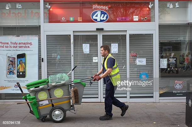 A street cleaner walking by a now closed Phones4u store in central Manchester