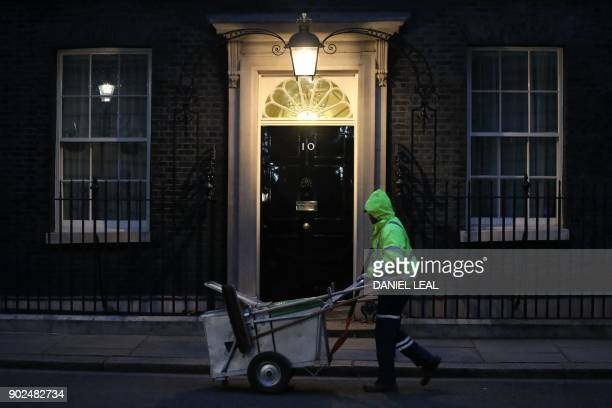 TOPSHOT A street cleaner walks past 10 Downing street on January 8 2018 British Prime Minister Theresa May is expected to reshuffle her cabinet today